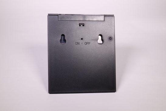 裏側にはON/OFFのボタンと壁掛け用の穴が開いています。 ON/OFFスイッチはクリップなどの細長い棒で押す必要があります。